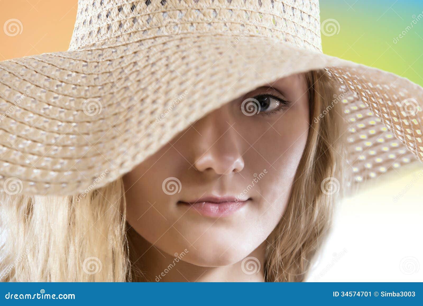 Mujer preciosa con cierre del sombrero del verano de la paja encima del retrato