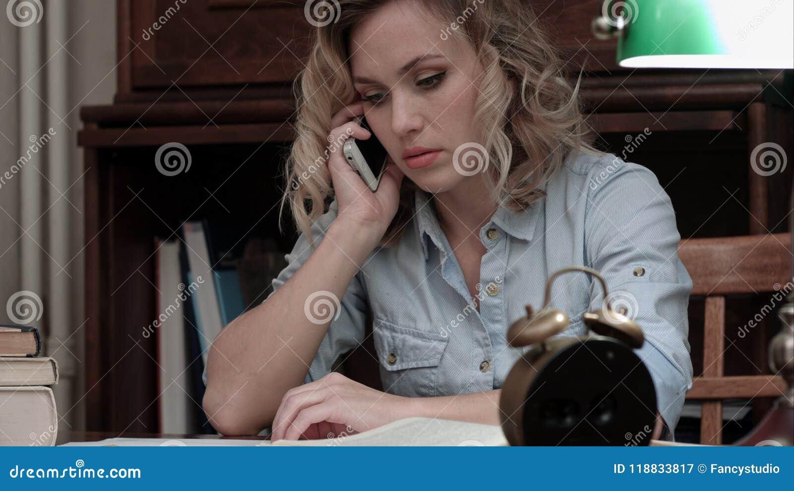Mujer preocupante que habla en el teléfono que se sienta en su lugar de trabajo
