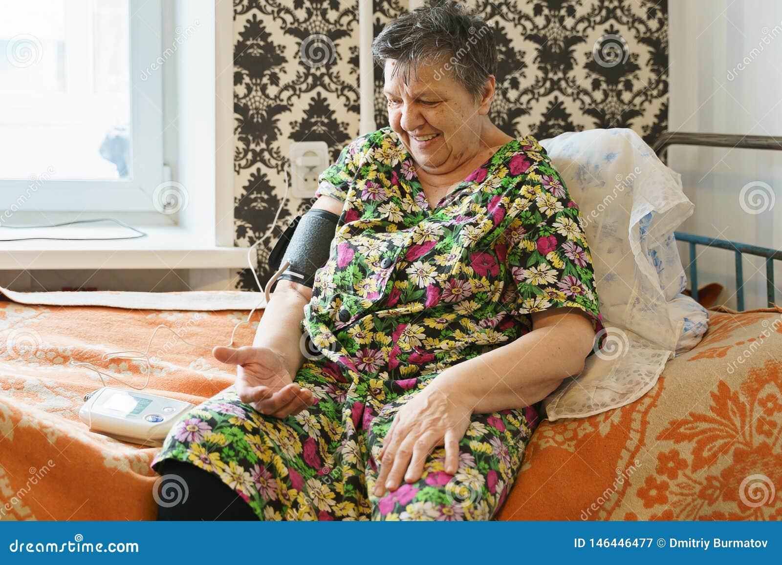 Mujer presi?n arterial de medici?n con tonometer misma