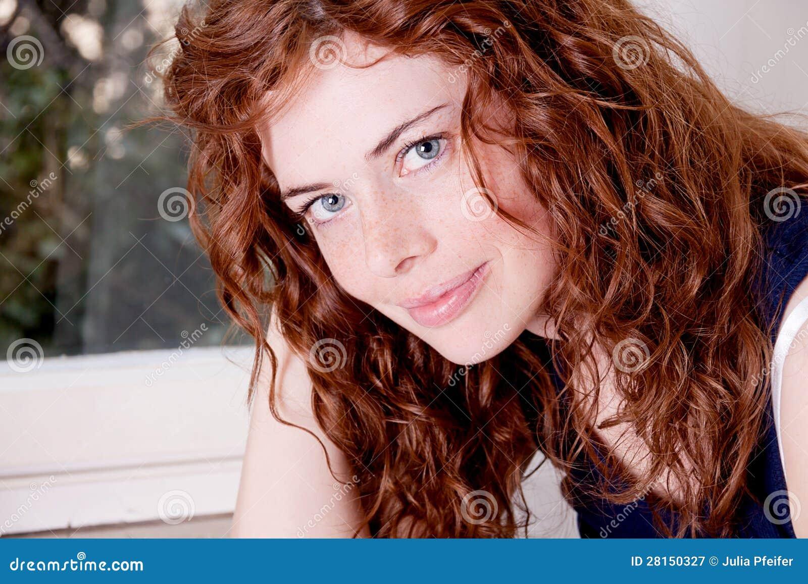 Mujer principal roja hermosa con la sonrisa de la peca