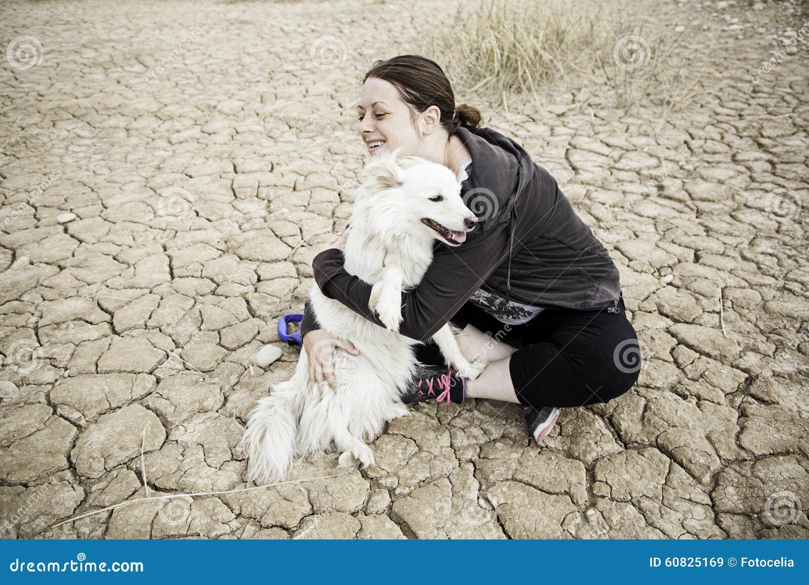 Mujer que abraza samoyedo