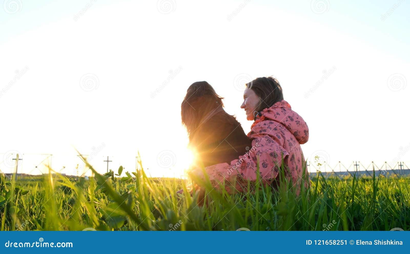 Mujer que abraza un perro en la puesta del sol, chica joven con un animal doméstico que se sienta en la hierba y que se relaja en