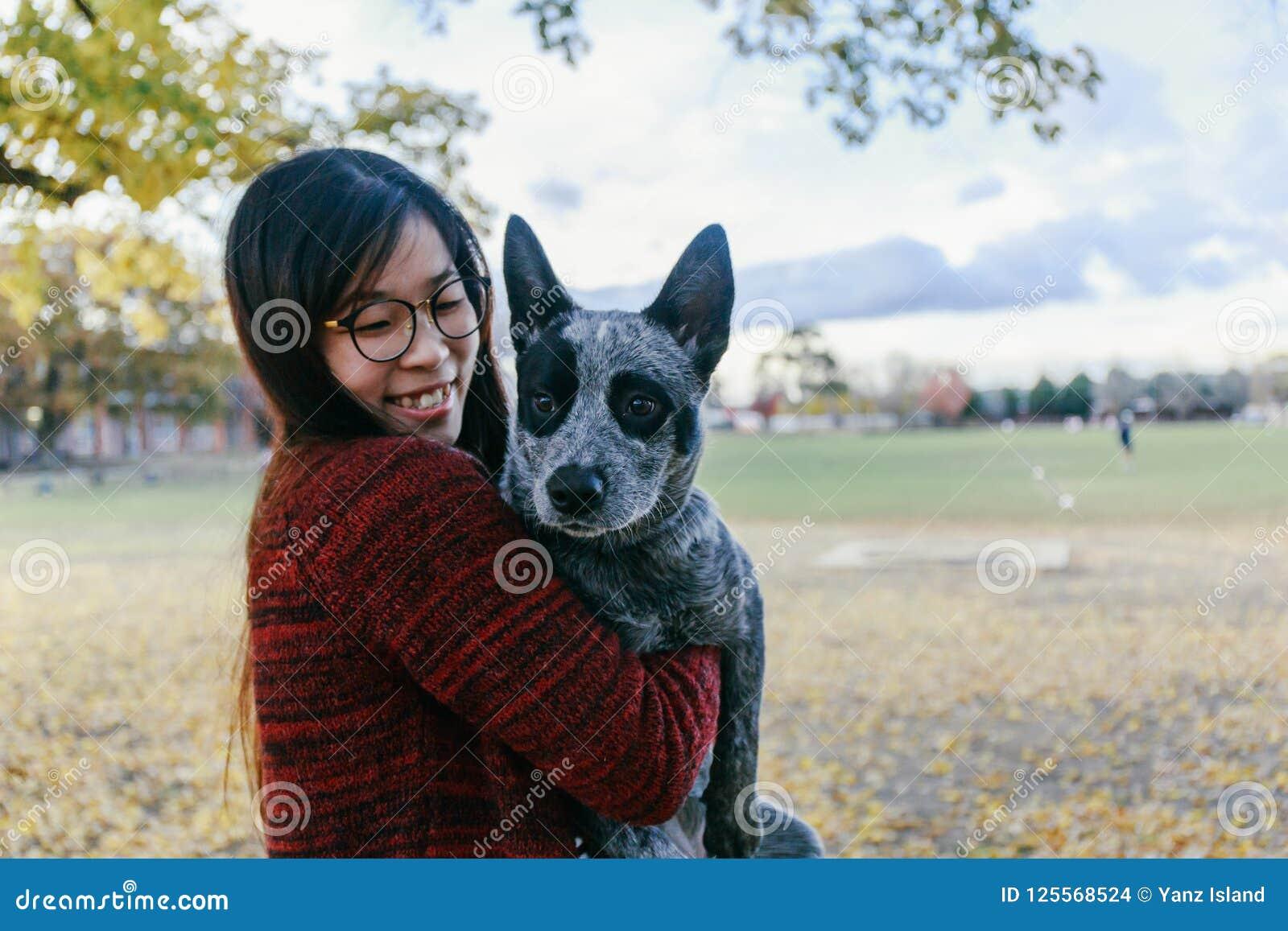 Mujer que abraza y que mira blando su perrito del australiano del animal doméstico
