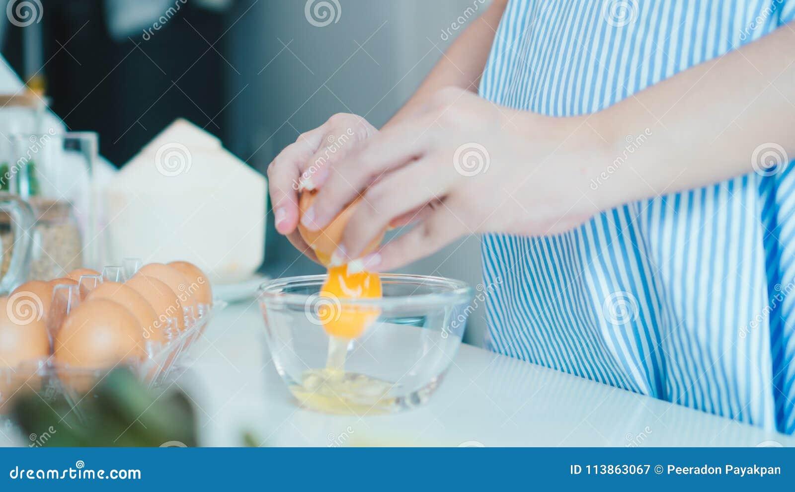 Mujer que agrieta un huevo en un cuenco con hacer una pausa en cocina