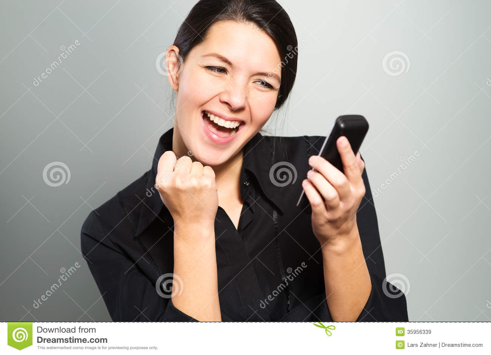 Mujer que anima en las buenas noticias en su móvil