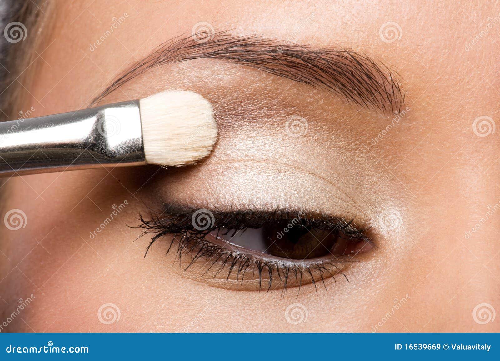 Mujer que aplica el sombreador de ojos en el párpado