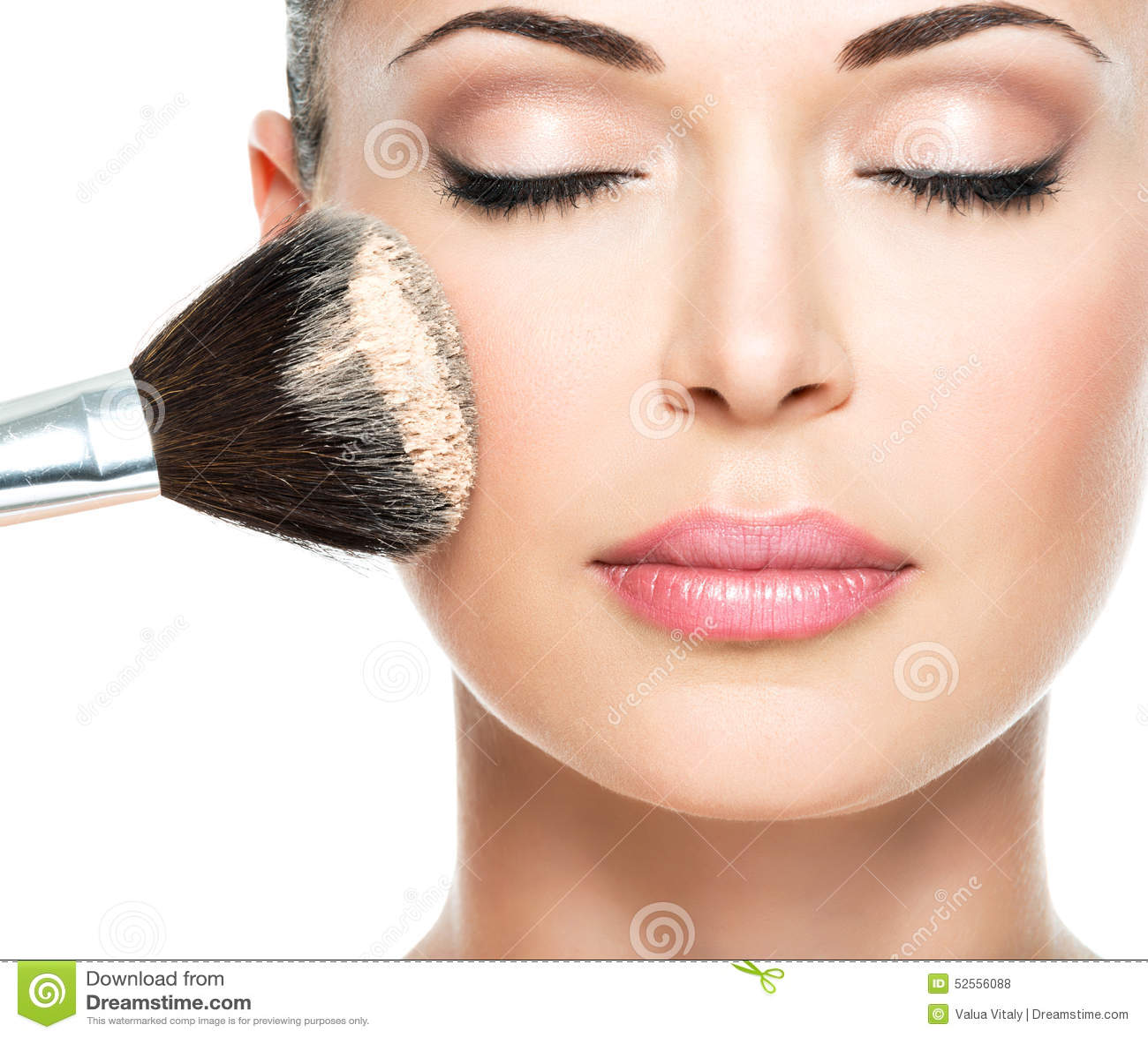 Mujer que aplica la fundación tonal cosmética seca en la cara