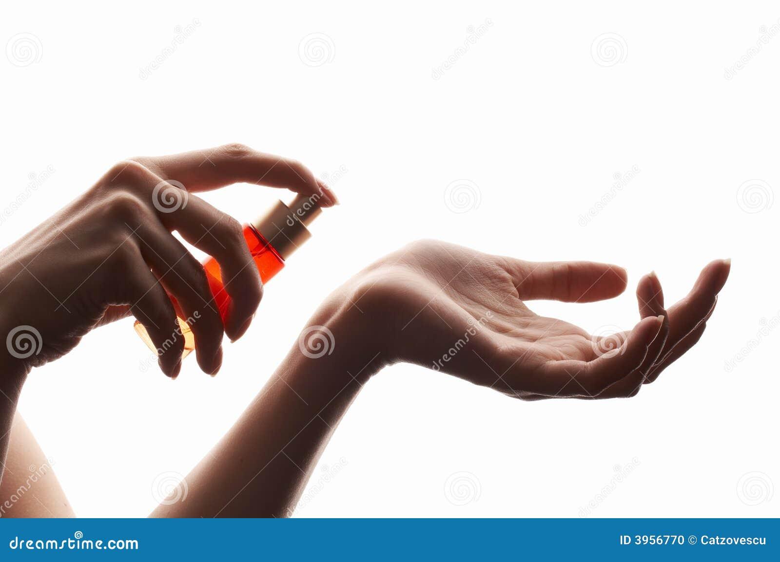 Mujer que aplica perfume en su muñeca