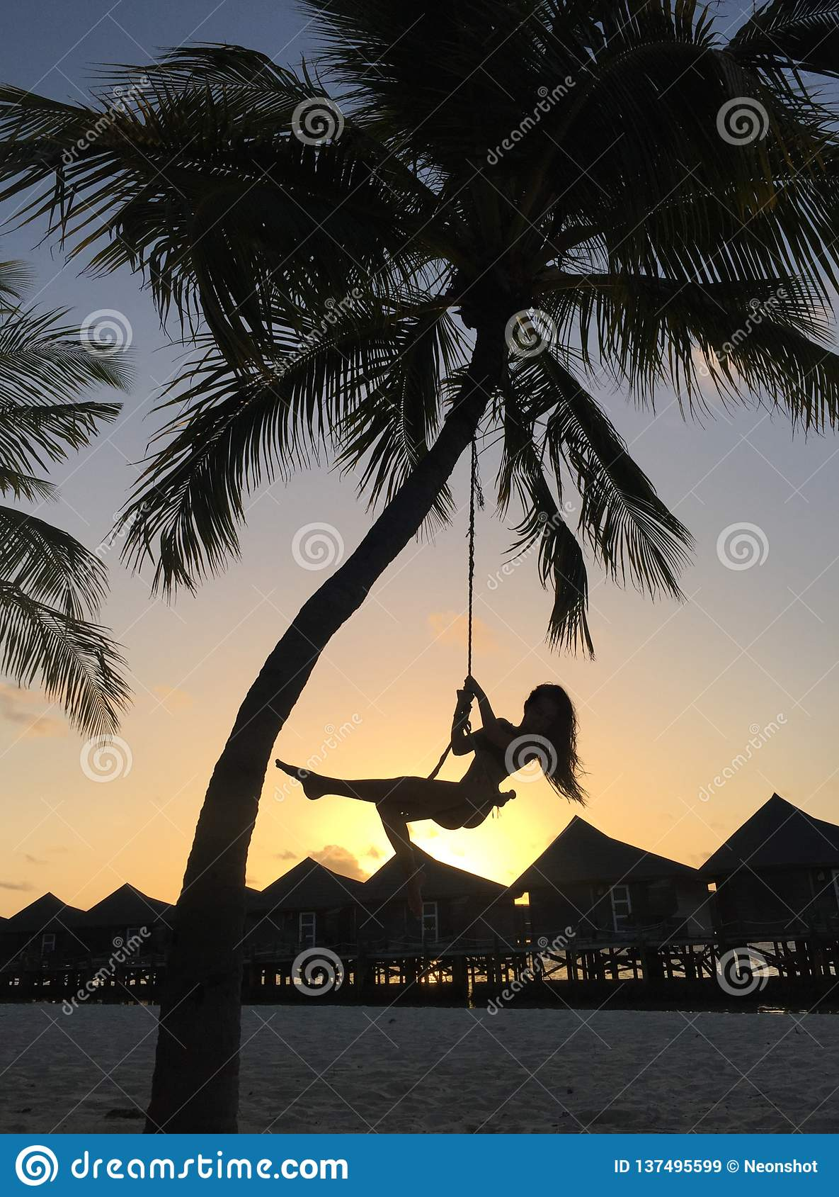 Mujer que balancea en la playa tropical