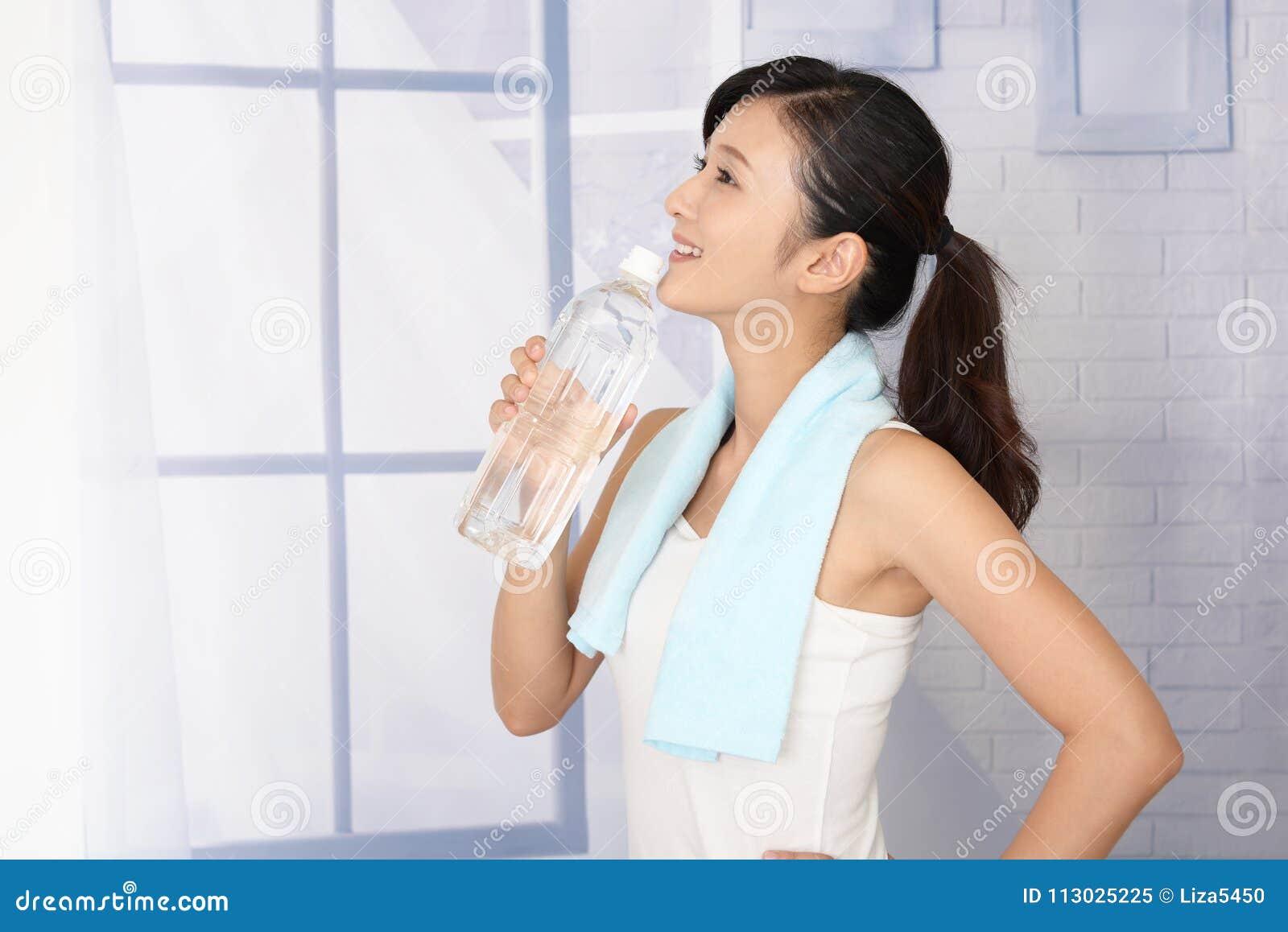 Mujer que bebe una botella de agua