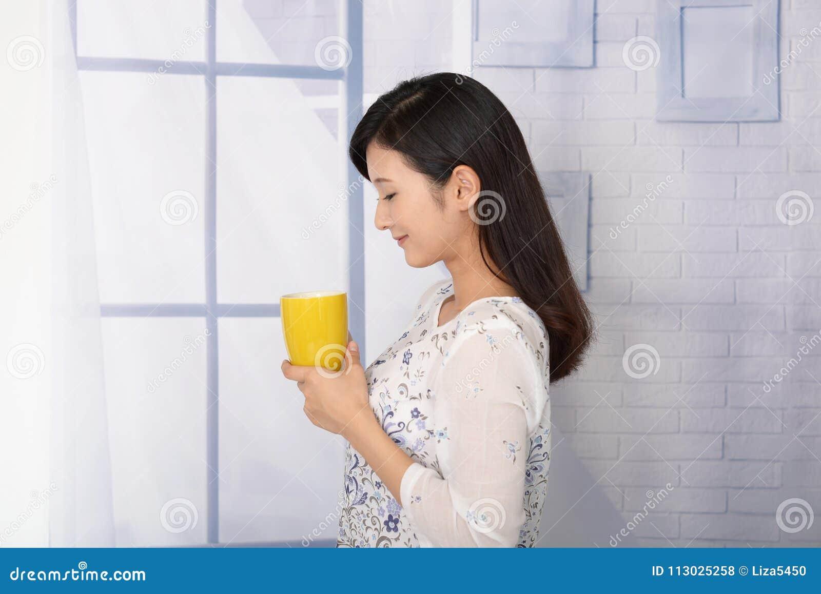 Mujer que bebe una taza de café