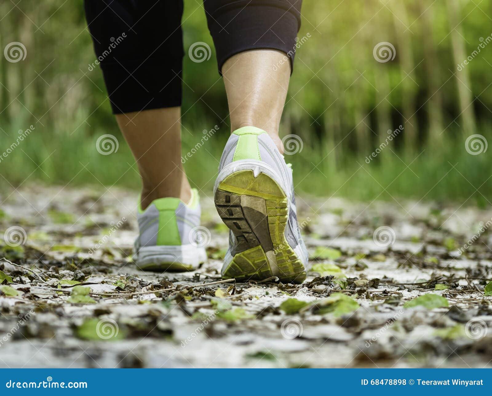 Mujer que camina en ejercicio que activa al aire libre del rastro
