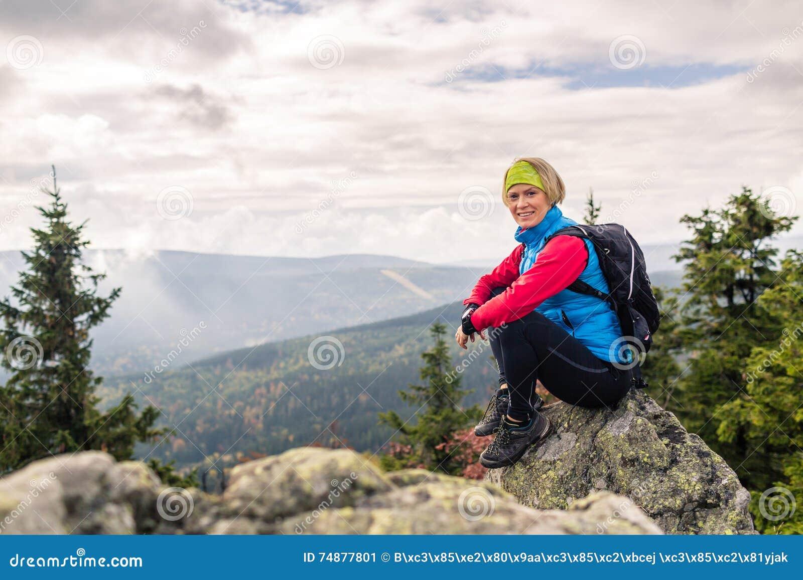 Mujer que camina en montañas y bosque del otoño