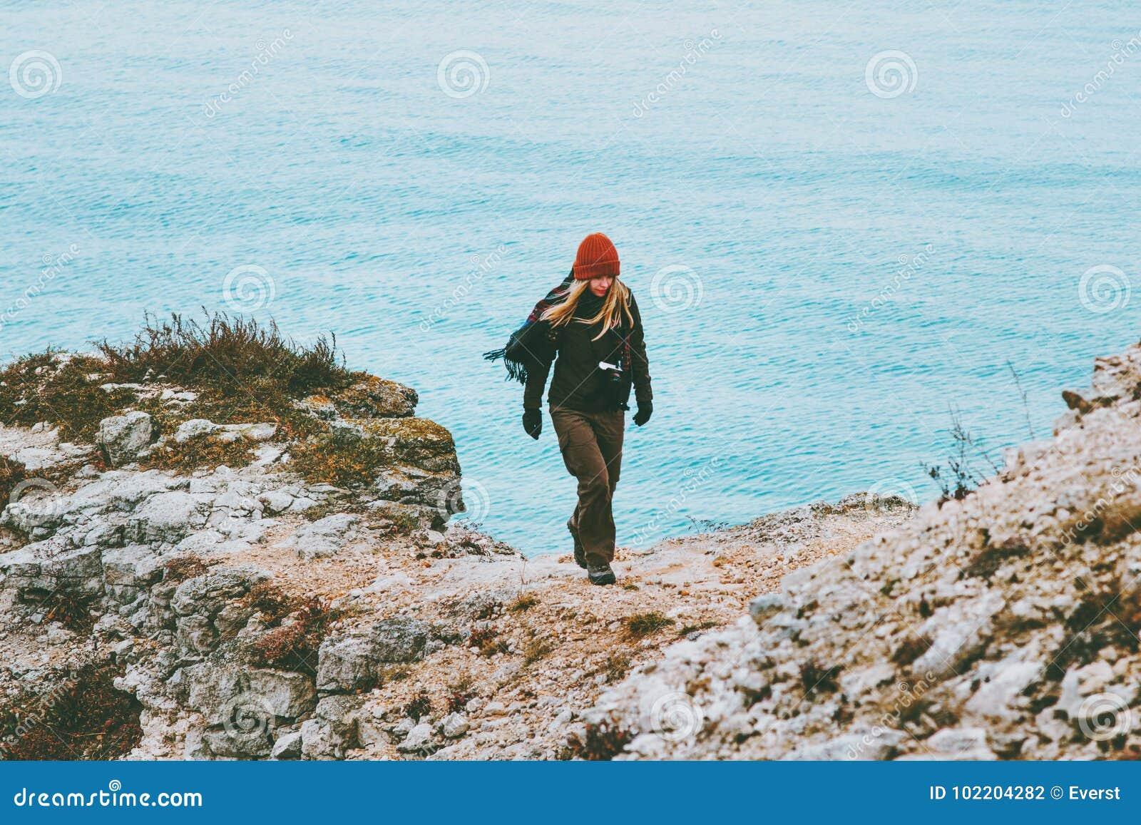 Mujer que camina solamente en el concepto frío de la forma de vida del viaje de la playa del invierno del mar