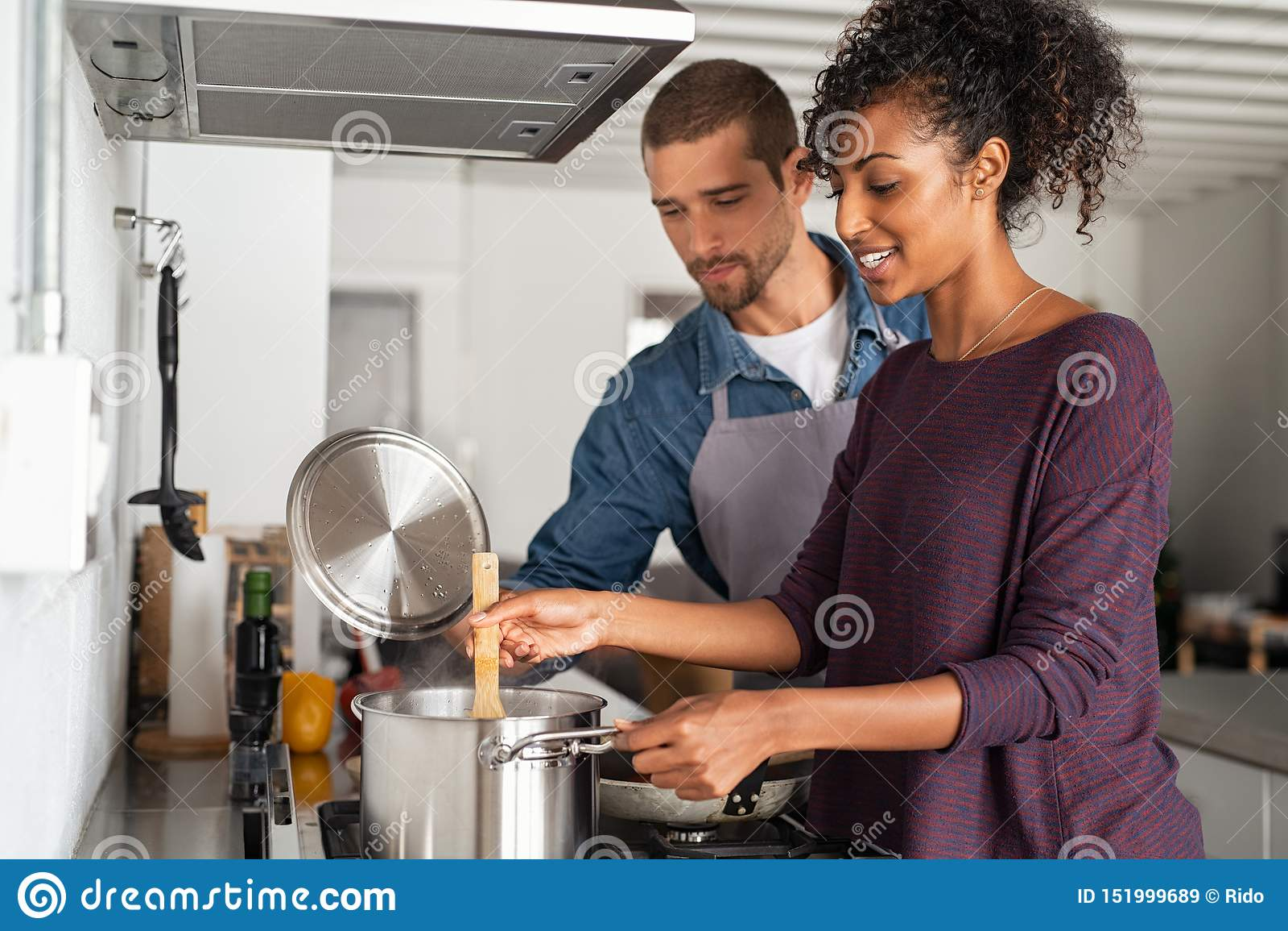 Mujer que cocina la comida con su novio