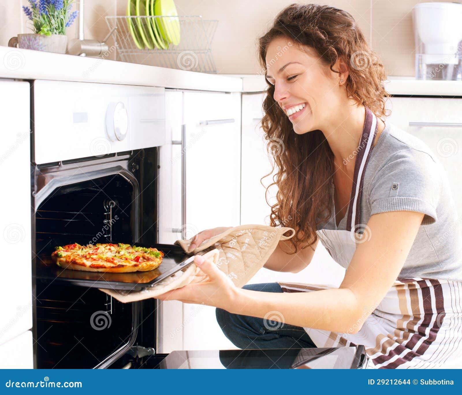 Mujer que cocina la pizza