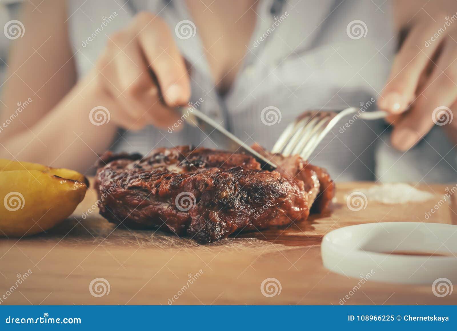 Mujer que come el filete asado a la parrilla delicioso