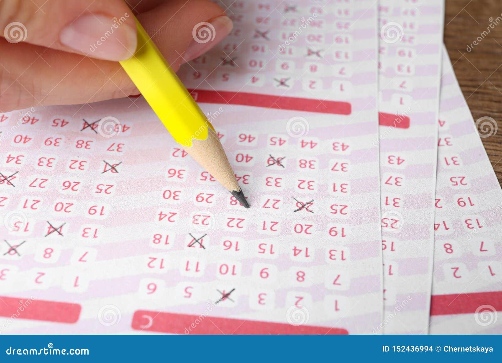 Mujer que completa boletos de lotería en la tabla de madera Espacio para el texto
