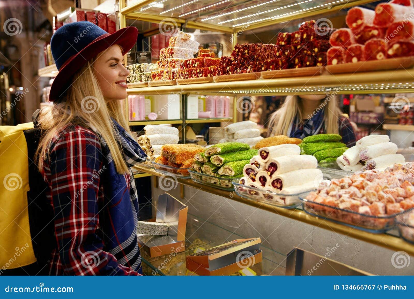Mujer que compra dulces turcos en el mercado del este de la comida
