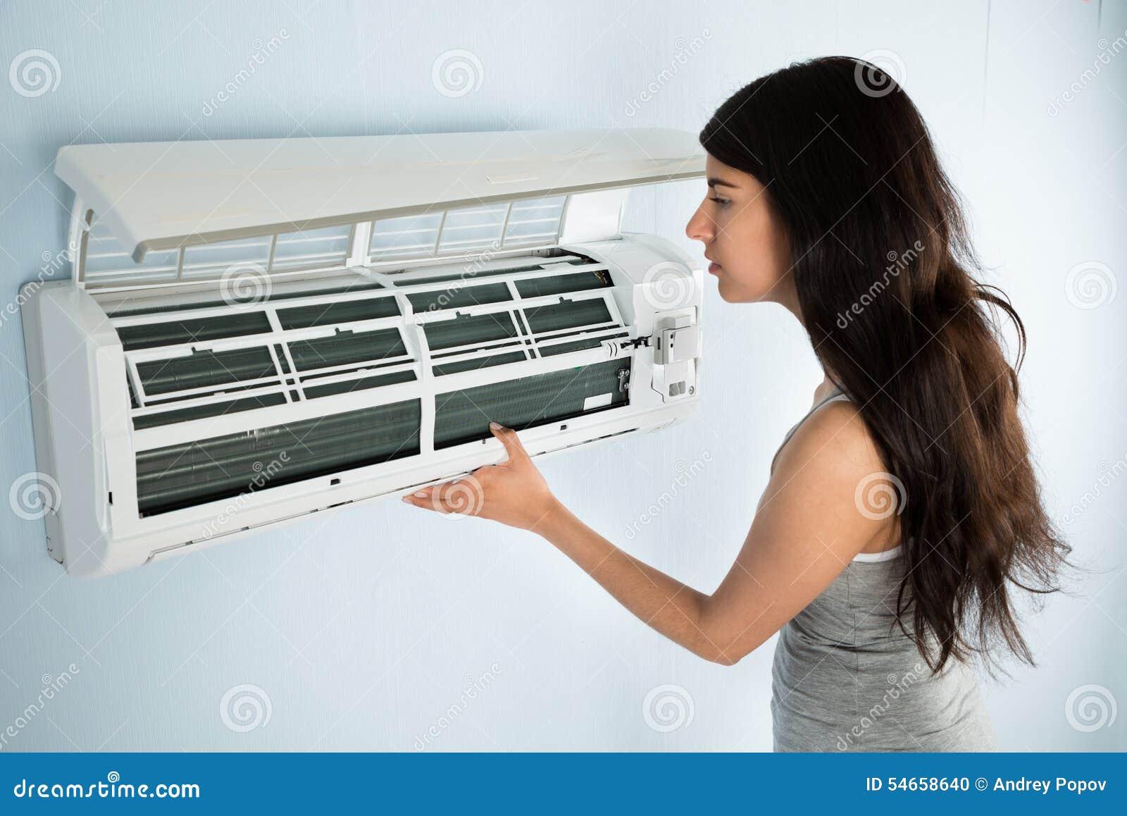 Mujer que comprueba el acondicionador de aire