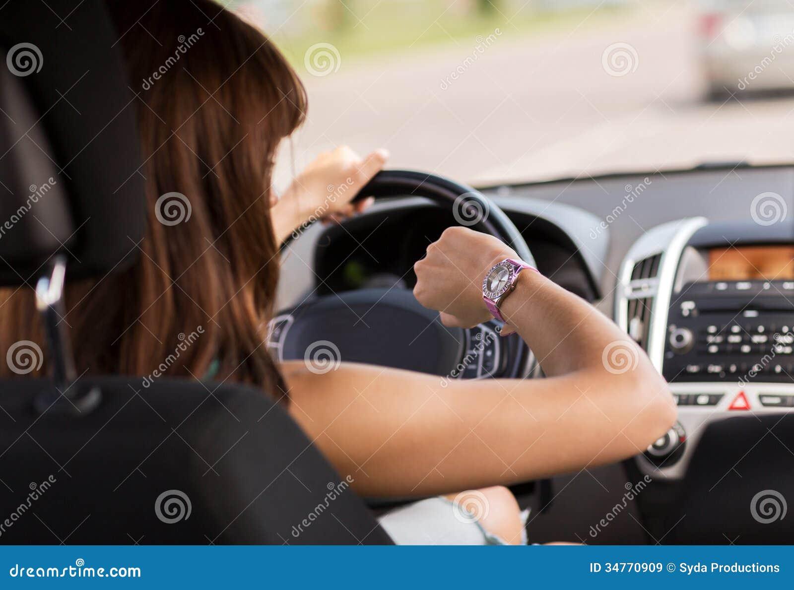 Mujer que conduce un coche y que mira el reloj