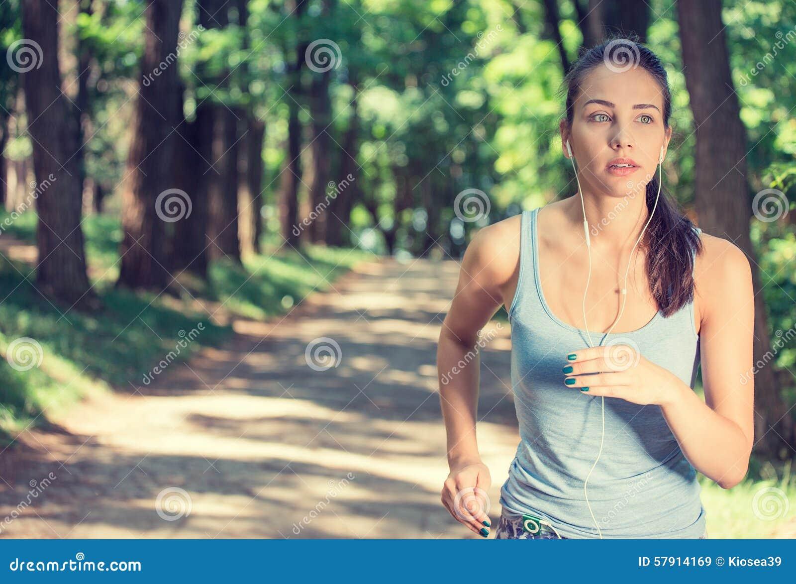 Mujer que corre en auriculares que llevan del campo