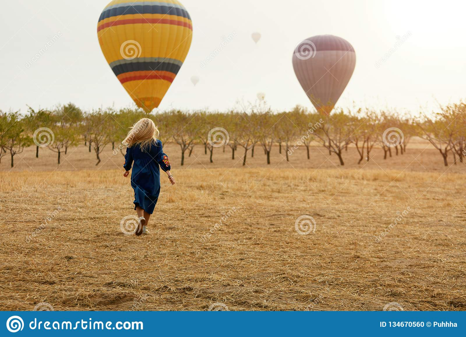 Mujer que corre en campo con el vuelo de los globos del aire caliente