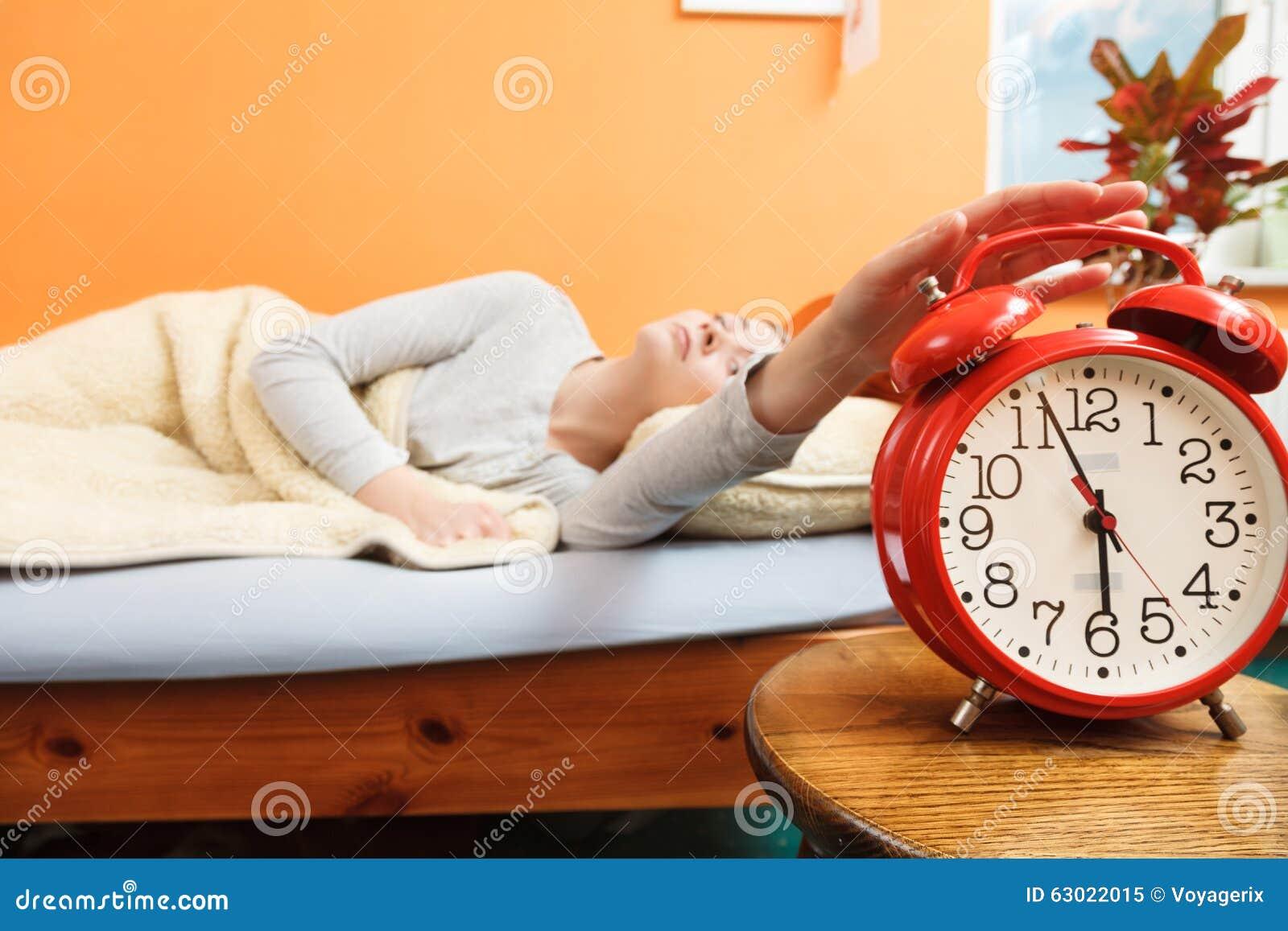 Mujer que despierta apagando el despertador por mañana