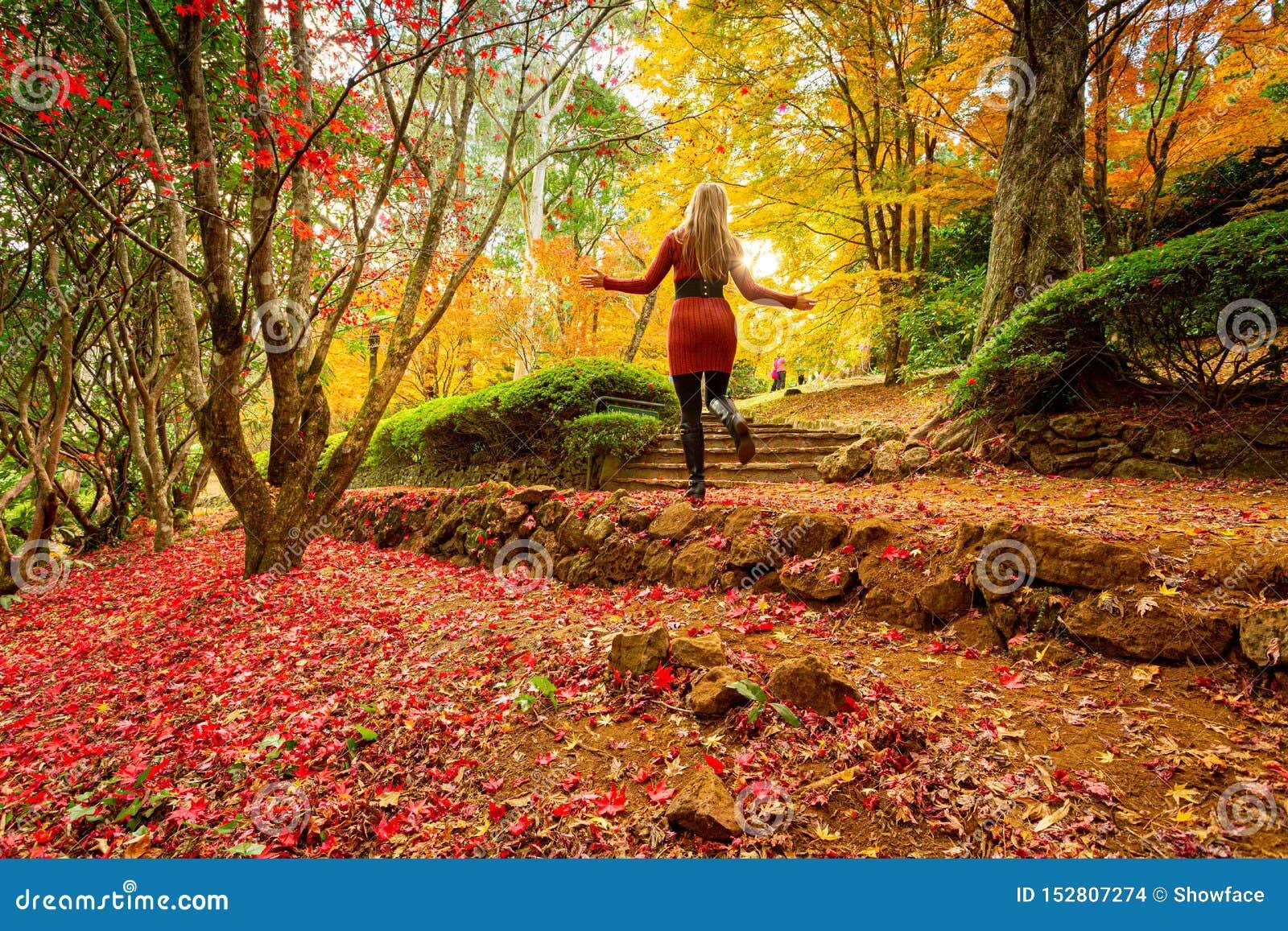 Mujer que disfruta de un paseo en un jardín del otoño