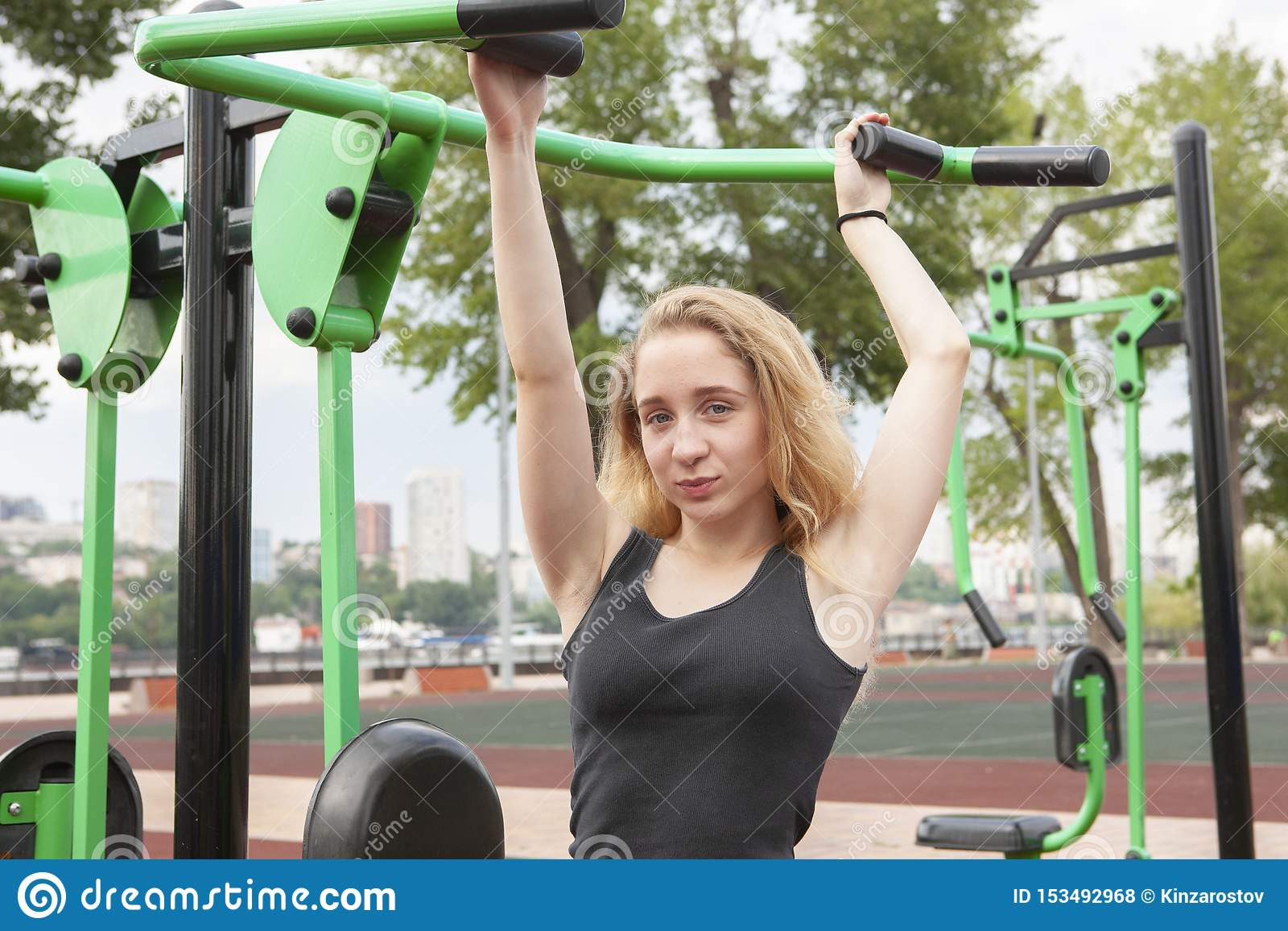 Mujer que ejercita con el equipo del ejercicio en el parque p?blico Mujer en una formaci?n en simulador de los deportes en el pat
