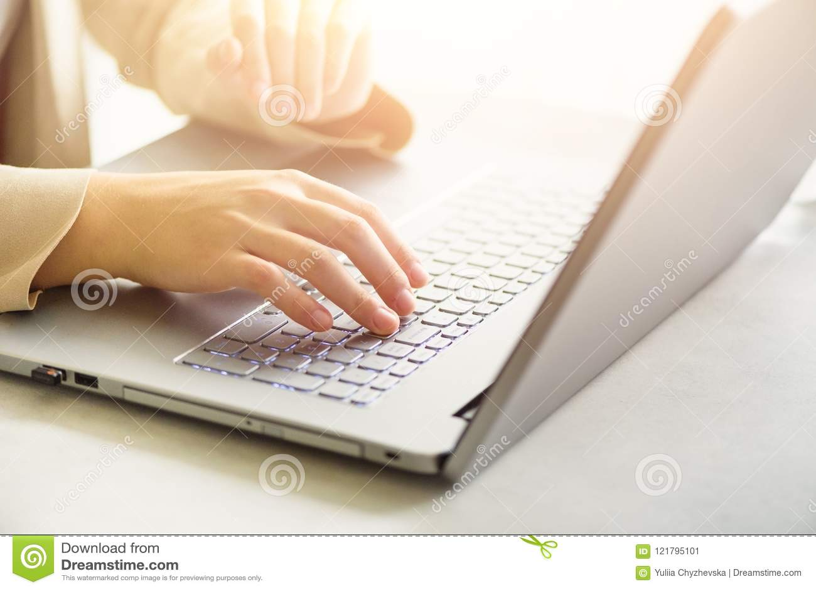 Mujer que elabora en cierre del ordenador La mujer da mecanografiar en el teclado del ordenador portátil, detalle en línea de las