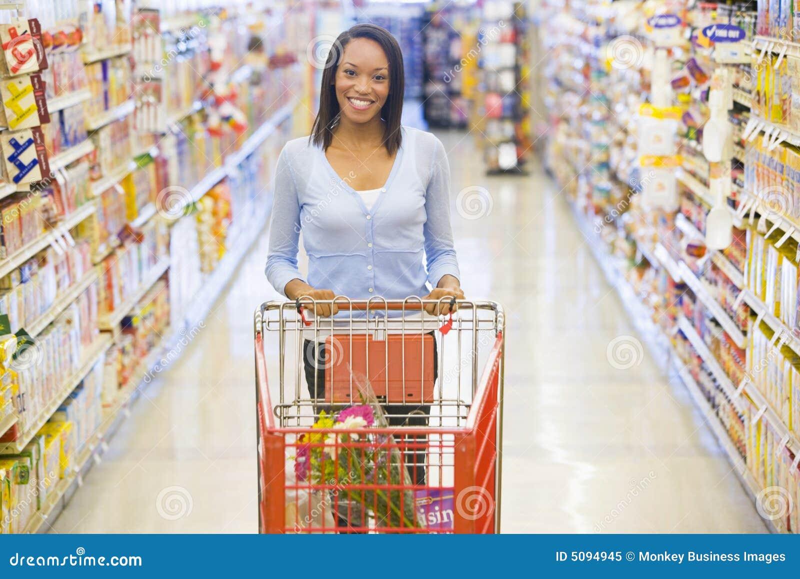 Mujer que empuja la carretilla en supermercado