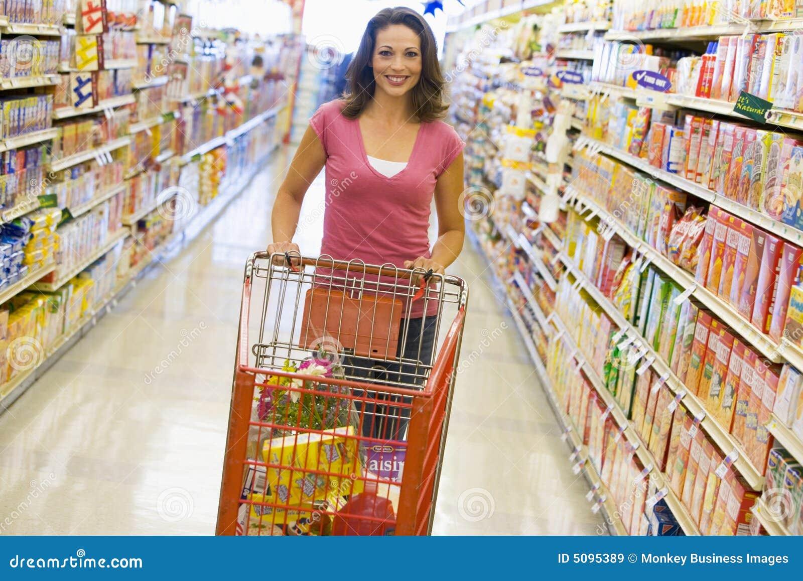 Mujer que empuja la carretilla a lo largo del pasillo del supermercado