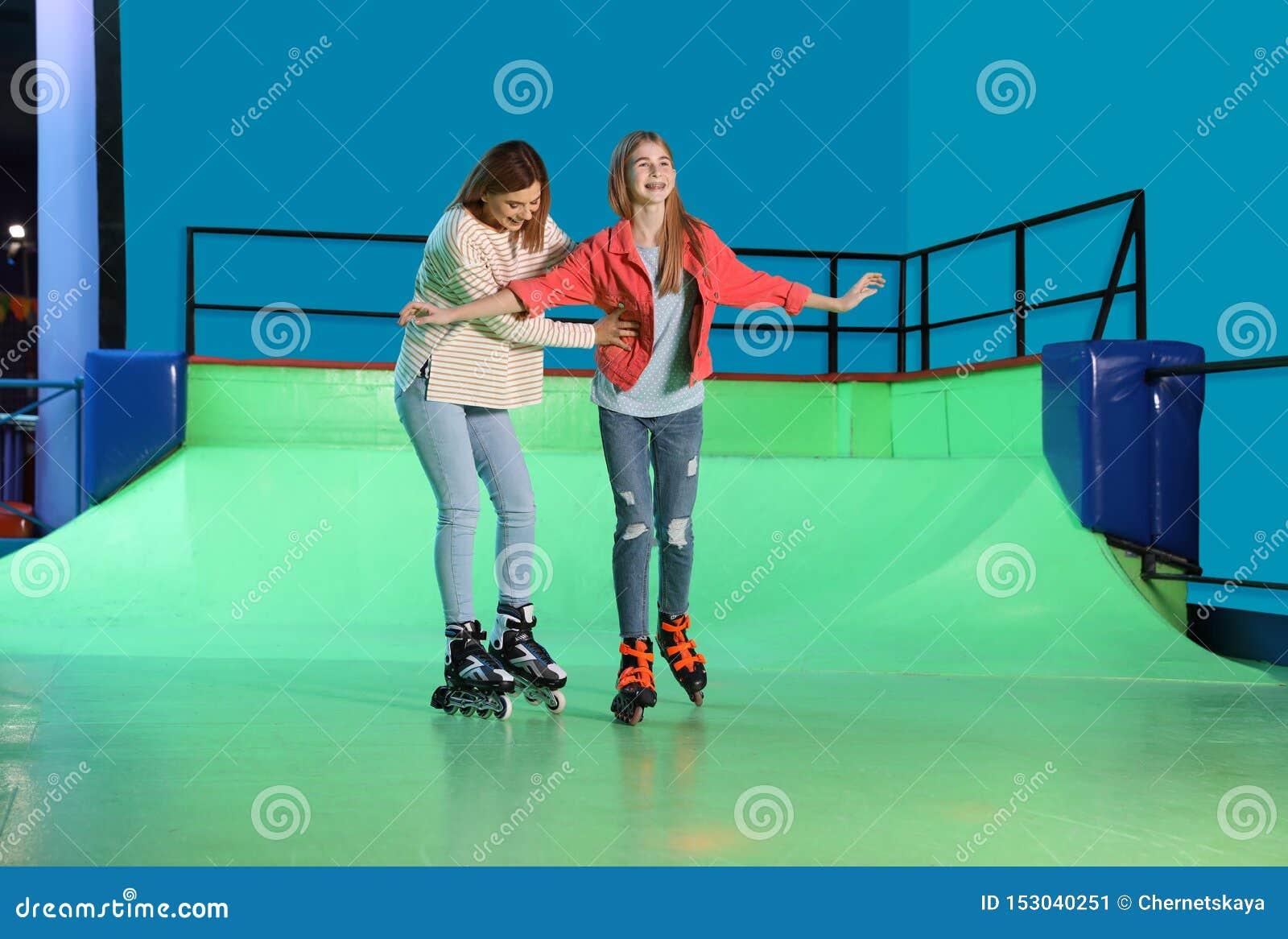 Mujer que enseña a su hija en la pista del rodillo