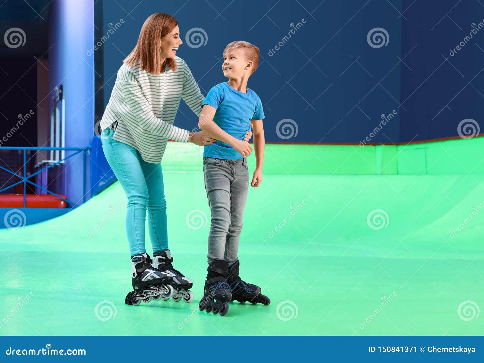 Mujer que enseña a su patinaje sobre ruedas del hijo en la pista