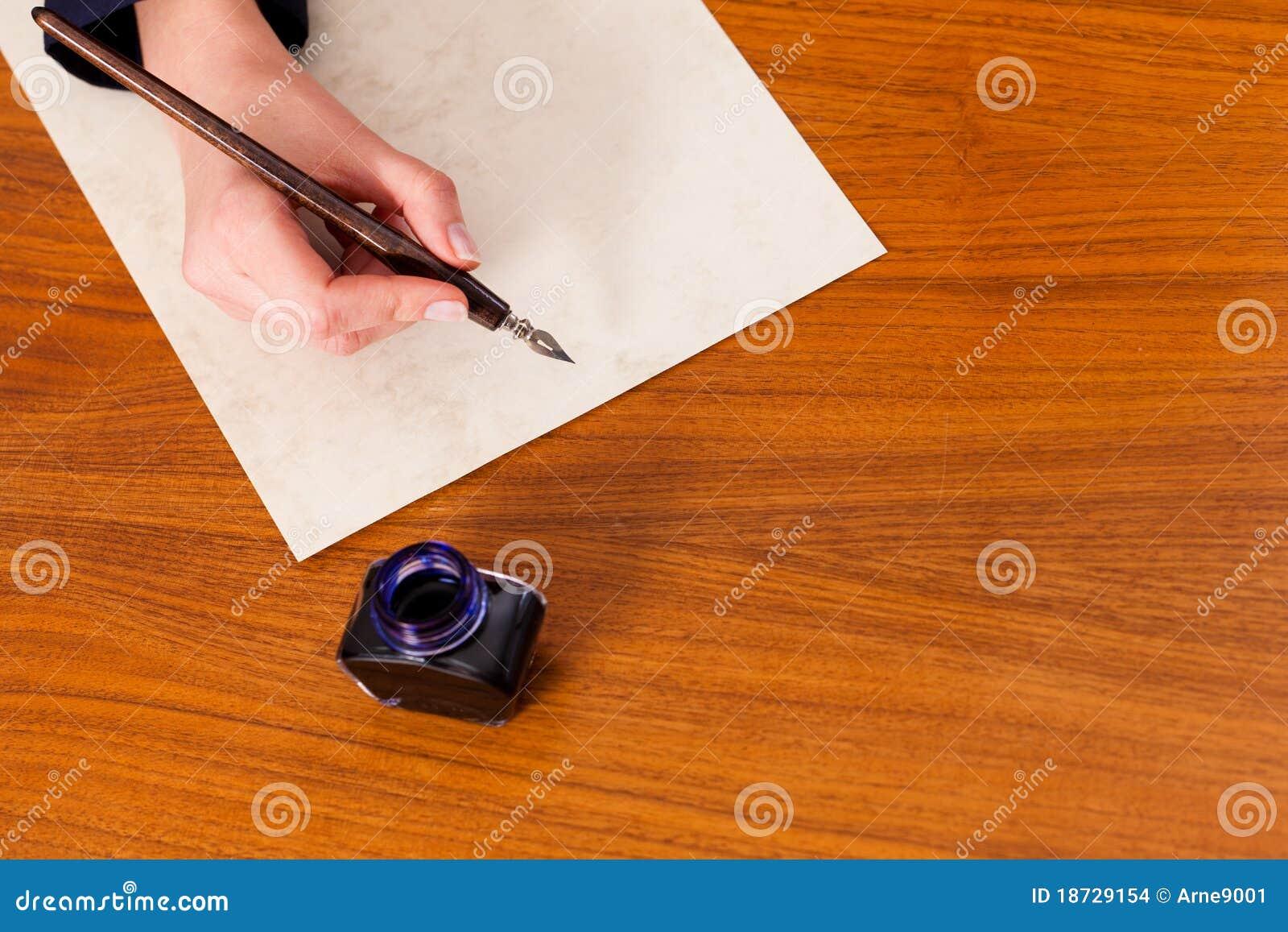 Mujer que escribe una letra con la pluma y la tinta