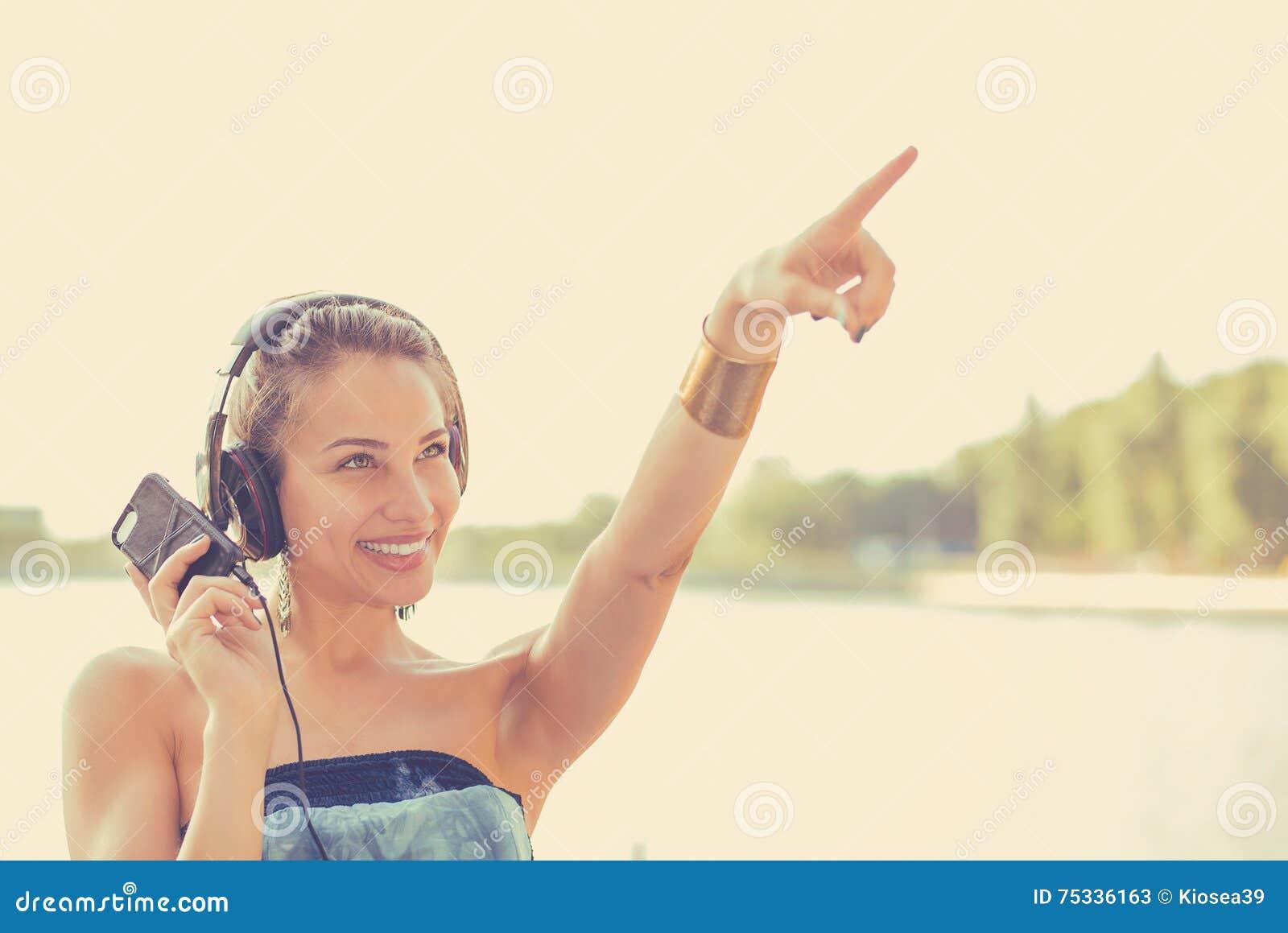 Mujer que escucha la música al aire libre