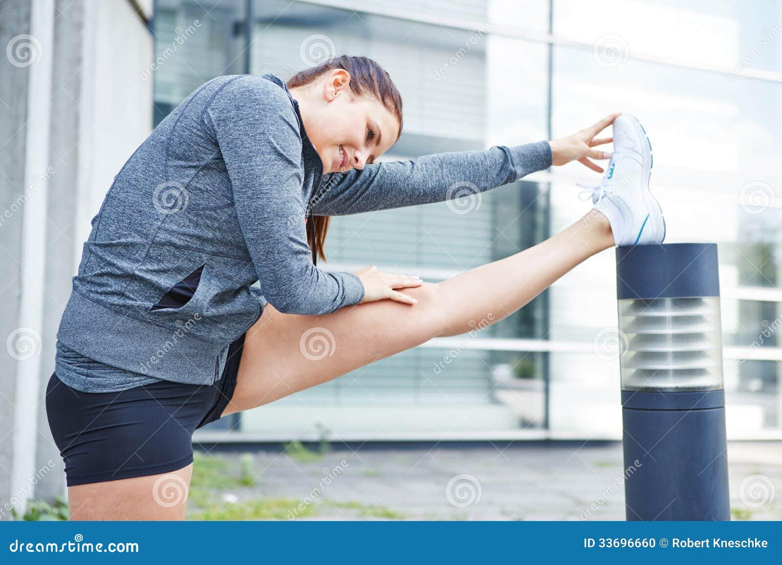 Mujer que estira sus piernas antes de correr