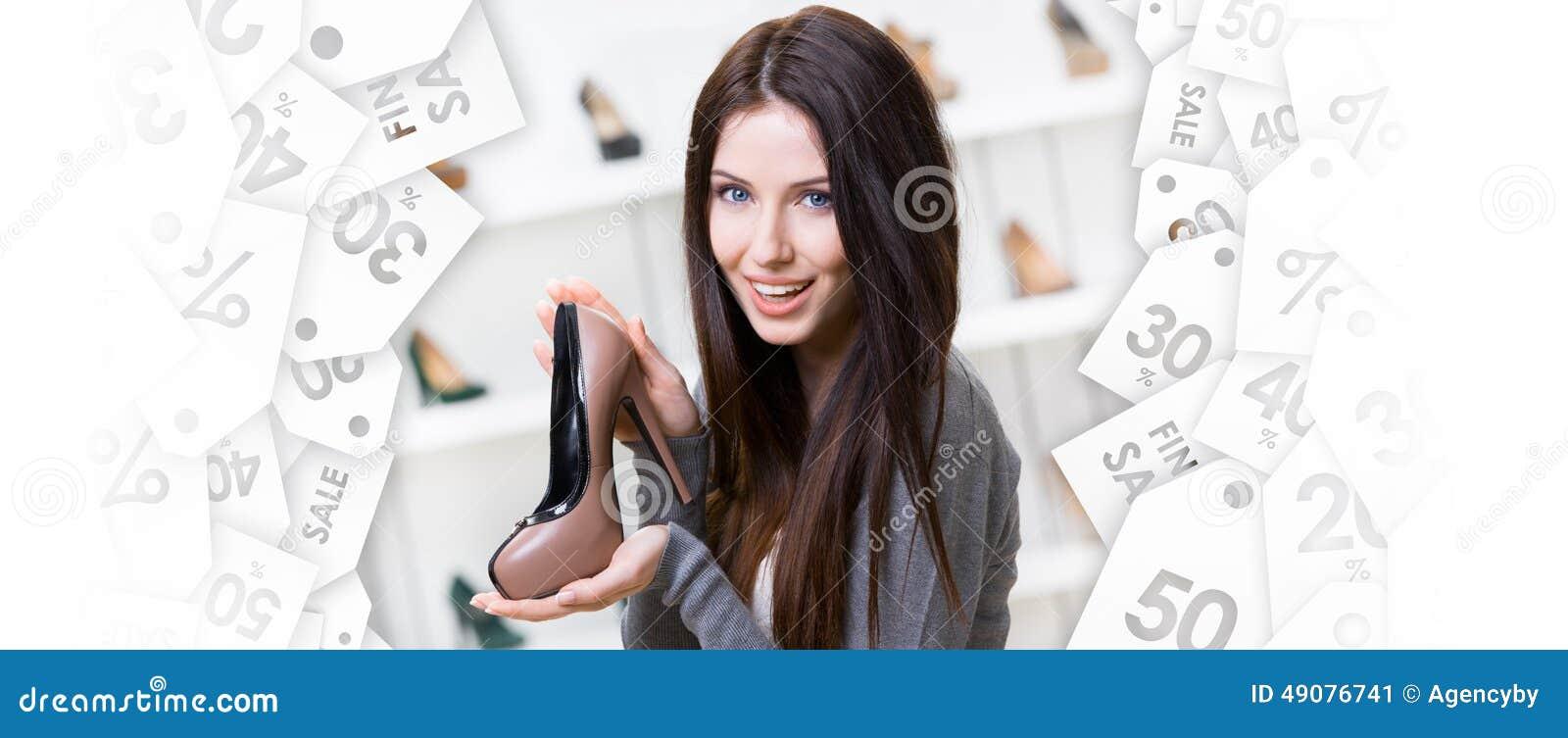Mujer que guarda el zapato café-coloreado Venta negra de viernes