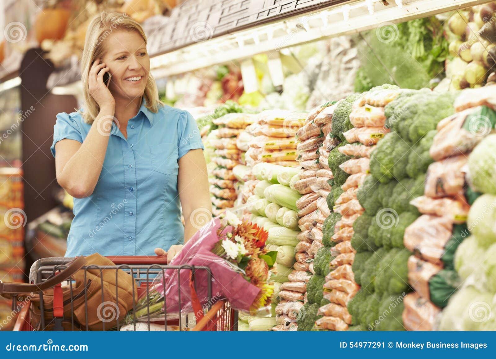 Mujer que habla en el teléfono móvil en supermercado