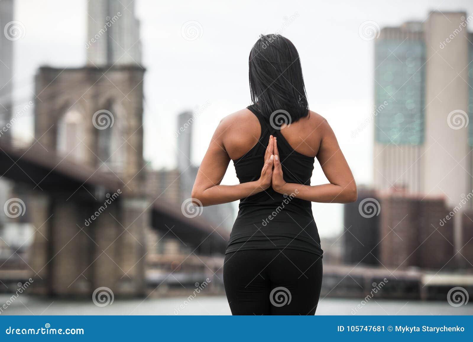 Mujer que hace actitud de la yoga con los brazos en la parte posterior en el parque de New York City La yoga clasifica concepto