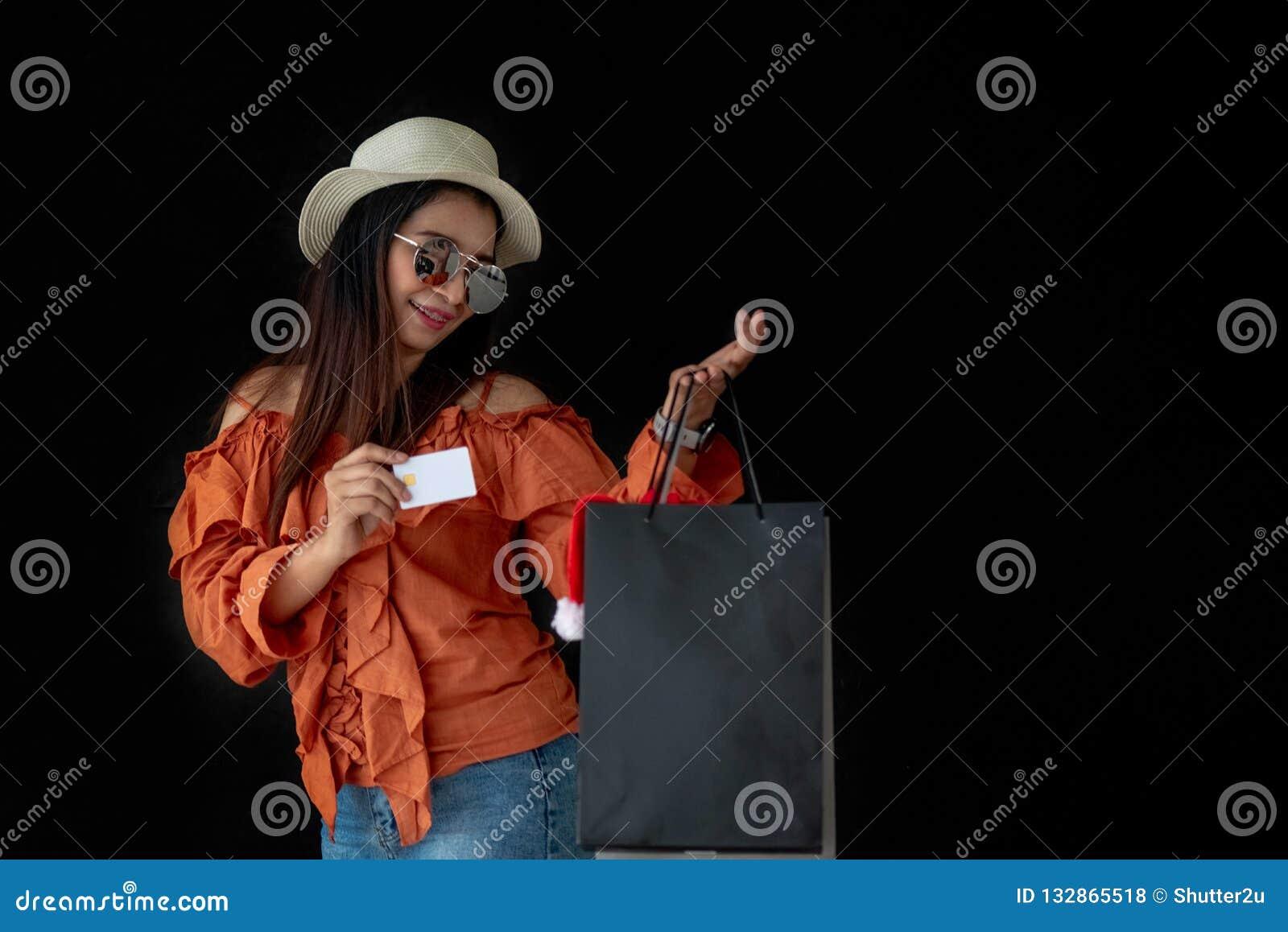 Mujer que hace compras asiática que sostiene la tarjeta de crédito con el shopp de Black Friday