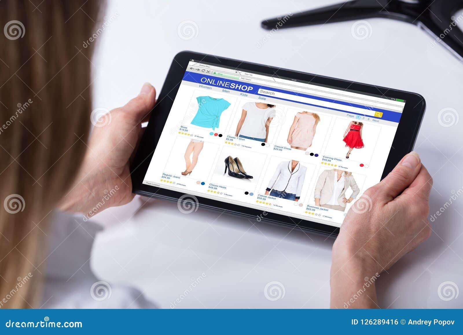 Mujer que hace compras en línea en la tableta de Digitaces