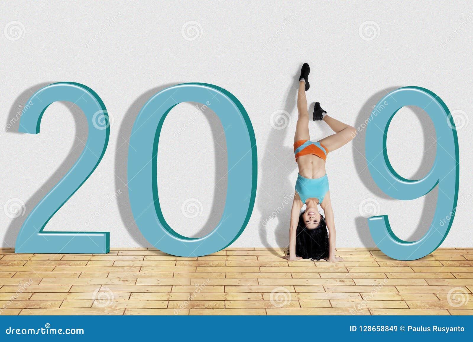 Mujer que hace ejercicio de la posición del pino con el número 2019