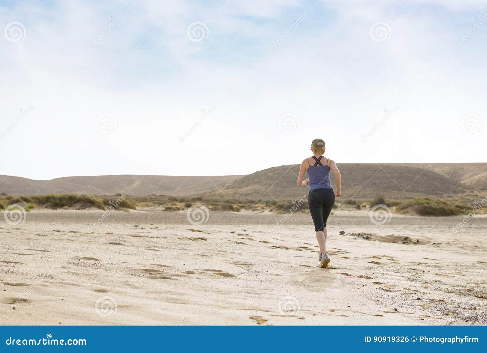 Mujer que hace la aptitud de la mañana corrida en el desierto