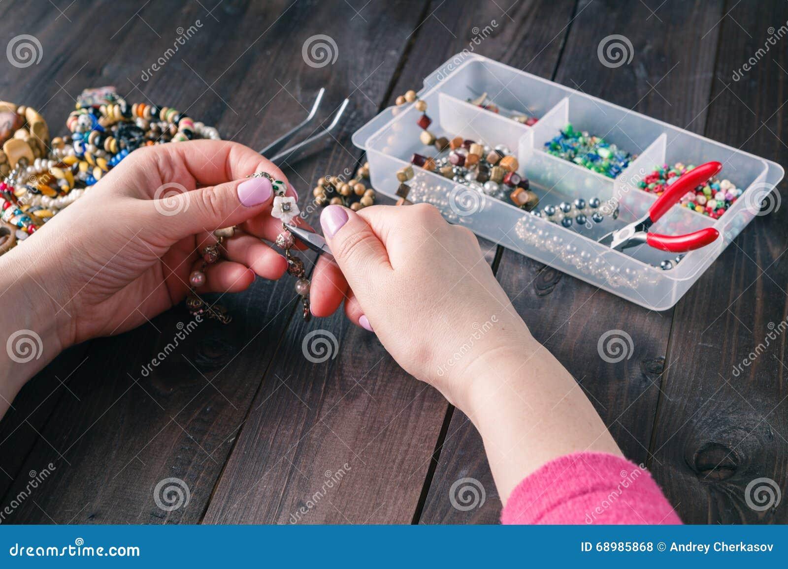Mujer que hace la pulsera moldeada con sus manos
