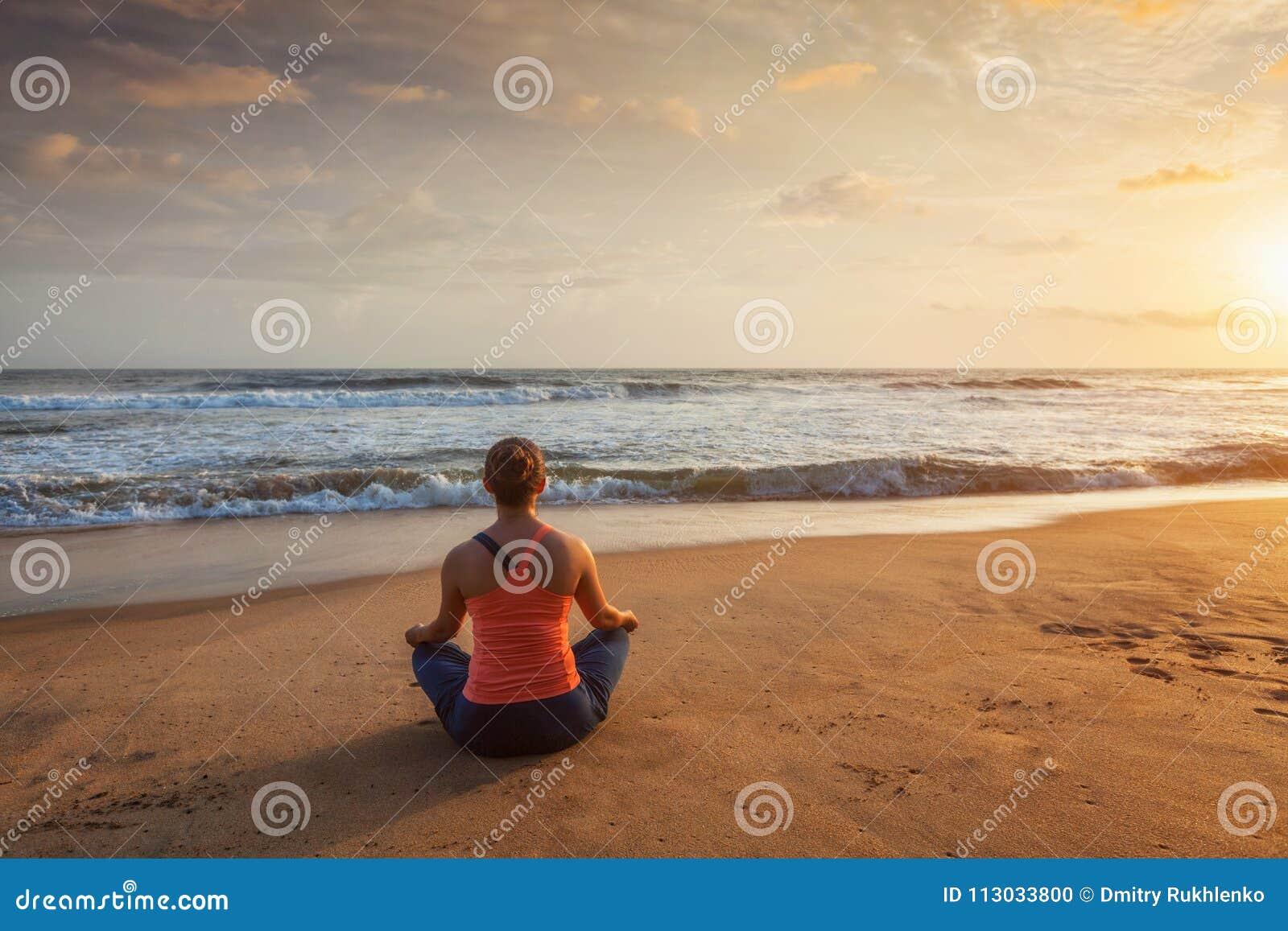 Mujer que hace oudoors de la actitud de Lotus de la yoga en la playa