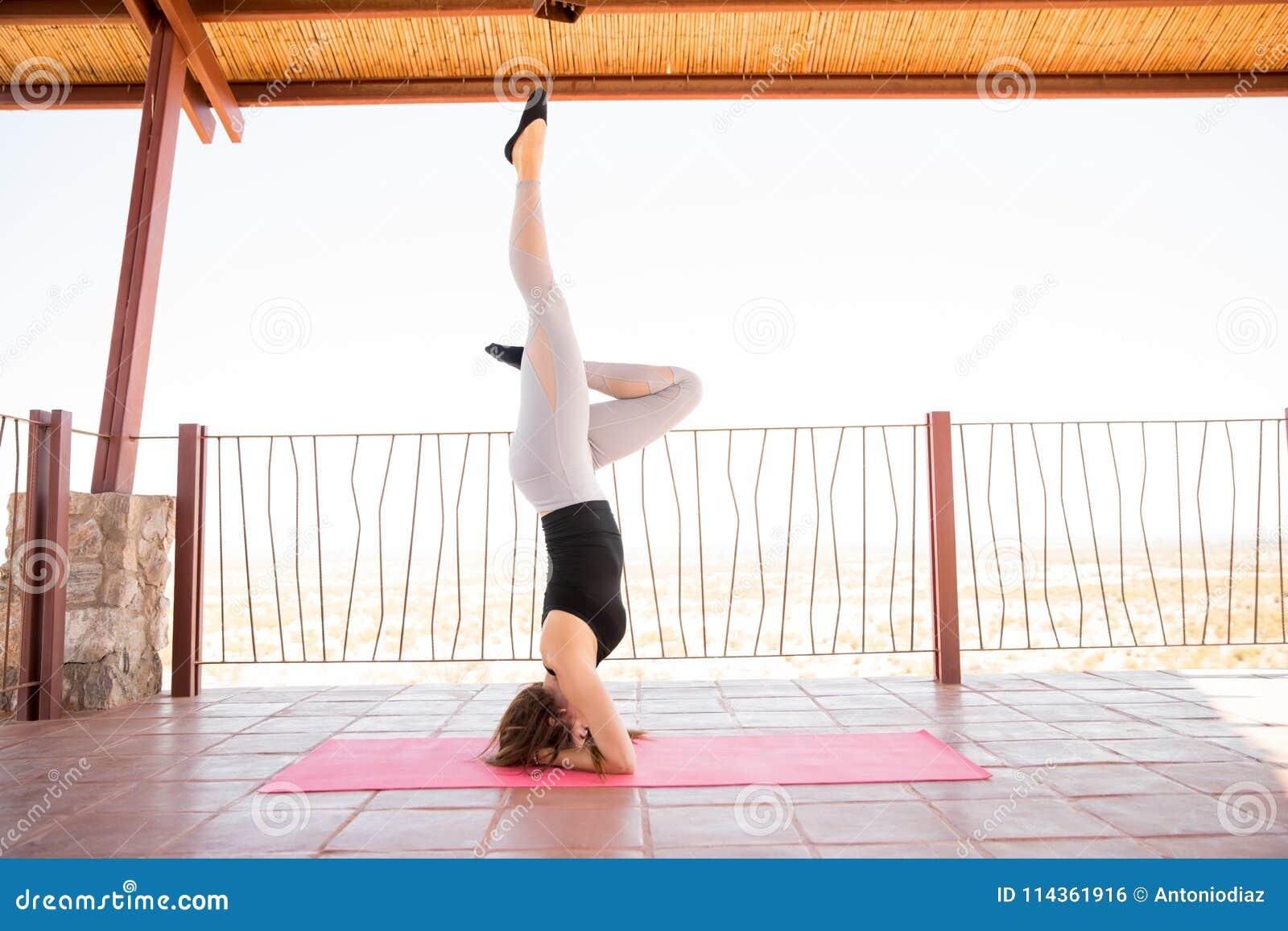Mujer que hace una yoga del headstand