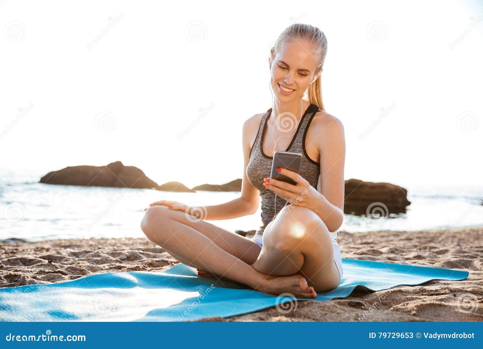 Mujer que hace yoga y que usa el teléfono celular que se sienta en la estera