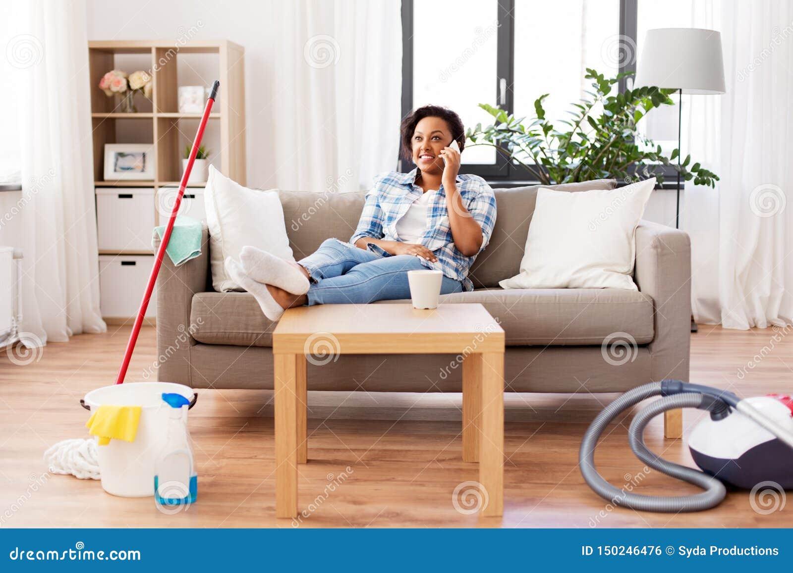 Mujer que invita a smartphone despu?s de la limpieza casera